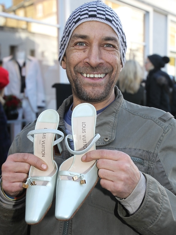 Happy customer holding a pair of Victoria Beckham's donated Louis Vuitton shoes