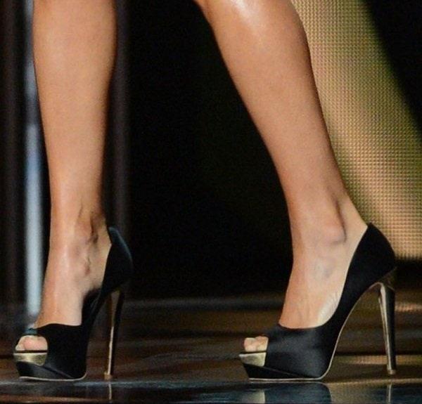 Carrie Underwood wears a pair of black satin peep-toe pumps from Rupert Sanderson on her feet