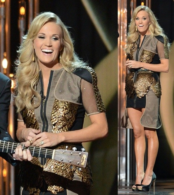 Carrie Underwood wears a black-and-gold outfit with mesh accents at the CMAs