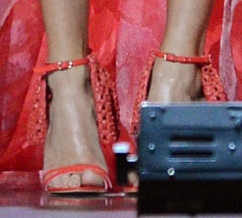 Carrie Underwood wears a pair of pink strappy sandals from Christian Siriano on stage