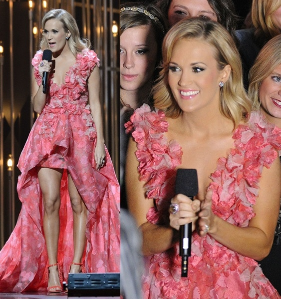 Carrie Underwood clutches her microphone while wearing a pink ruffled gown at the CMAs