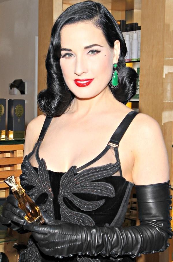 Dita Von Teese carries a bottle of her Erotique Dita Von Teese perfume