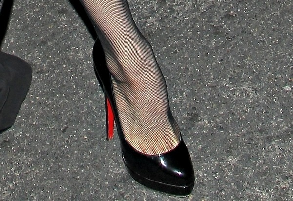 Dita Von Teese shows off her feet in Christian Louboutin pumps and black fishnet stockings