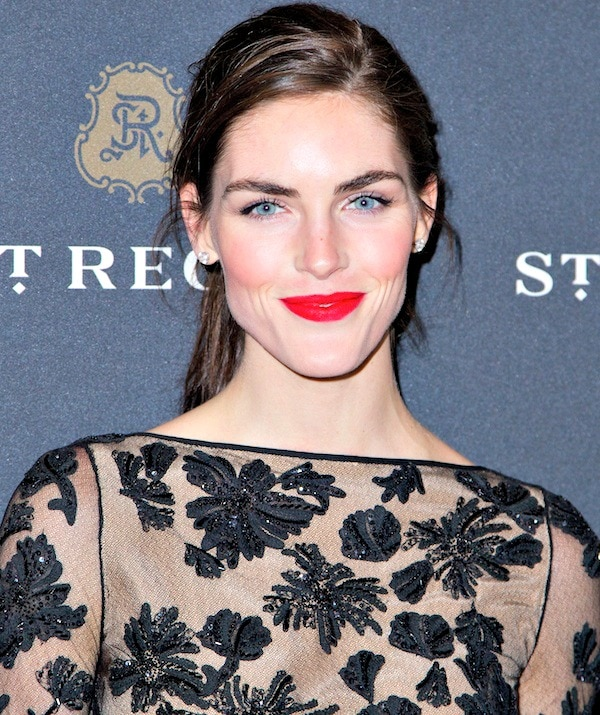 Hilary Rhoda's hair was styled in a messy ponytail, which showed off her stunning blue eyes, bright red lips, and beautiful earrings