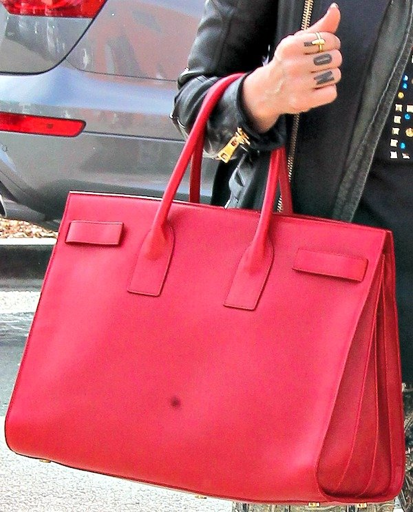 "Jessica Alba carried a scene-stealing bright red leather ""Sac de Jour"" bag from Saint Laurent"