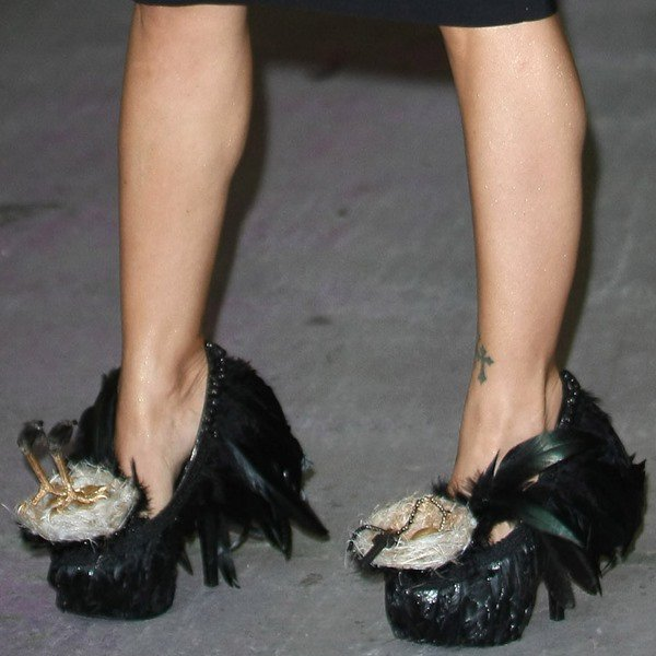 Jodie Marsh wearing heels featuring tiny birds' nests laden with eggs, a crucifix, the feet of a real crow, and a lot of black feathers