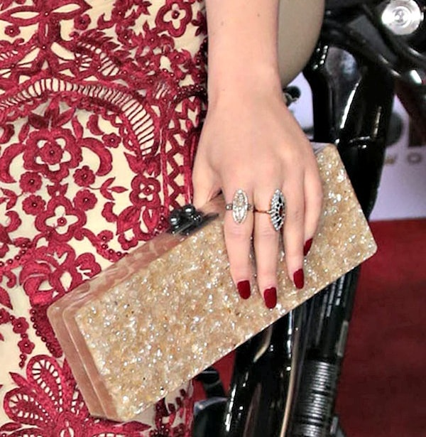 Kat Dennings toting a gold clutch by Edie Parker