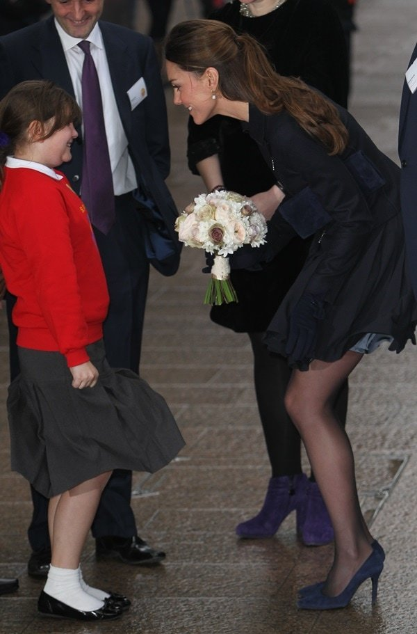 Kate Middleton trying to keep her skirt from getting blown by the wind as she receives a bouquet of flowers from a little girl at a Place2Be charity event in London on November 20, 2013