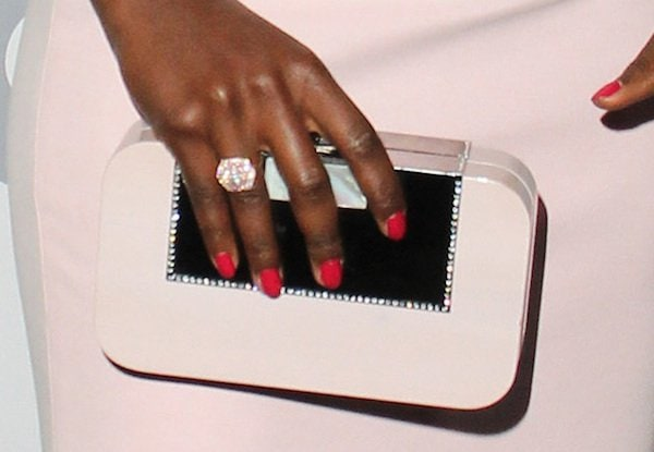 Lupita carried a pale pink wooden clutch from Devi Kroell