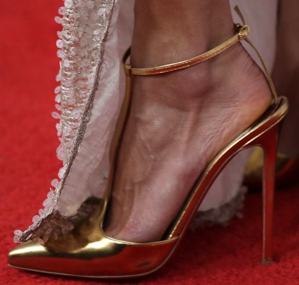 "Alessandra Ambrosio showing off her feet in metallic-gold t-strap ""T-Piga"" pumps by Christian Louboutin"