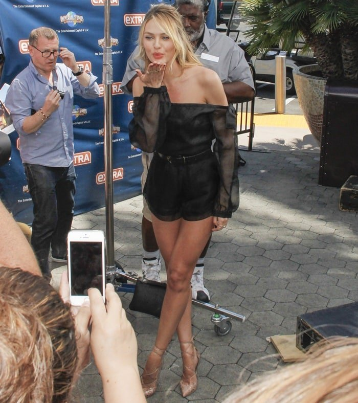 Candice Swanepoel blows kisses while making an appearance on Extra