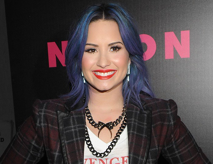 Demi Lovato with red lipstick and blue hair at the Nylon December issue party