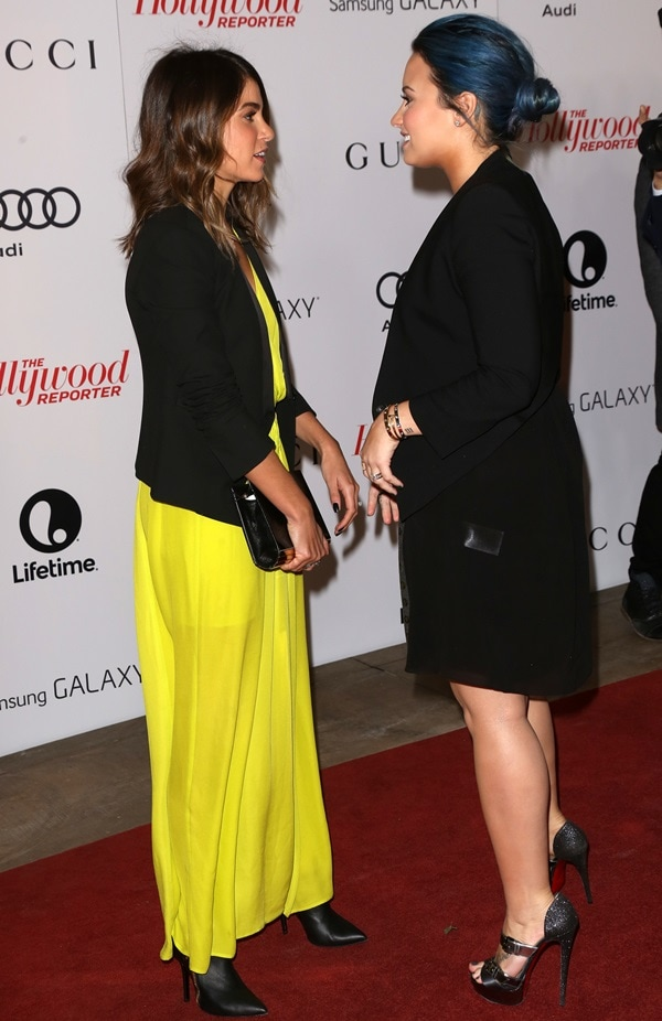 Joining Naya Rivera and Demi Lovato on the red carpet, Nikki Reed styled a neon yellow smocked surplice maxi dress by Charles Henry with a tall LOFT scuba twill jacket