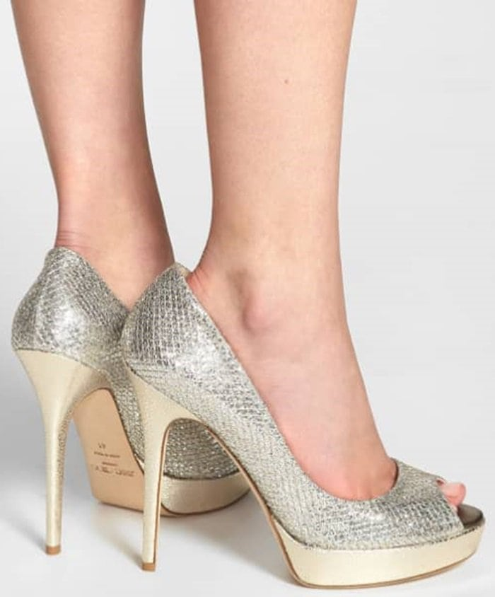 Glittering, textured fabric styles a peep-toe pump lifted by a lofty wrapped heel and platform