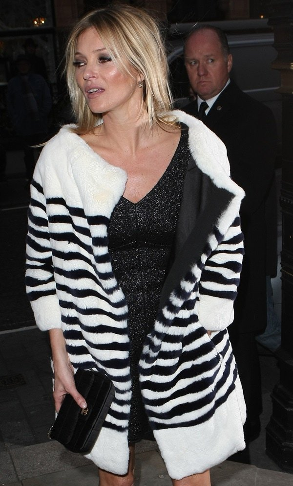 Kate Moss in a striped rabbit fur coat by Marc Jacobs paired with a Chanel evening shoulder bag