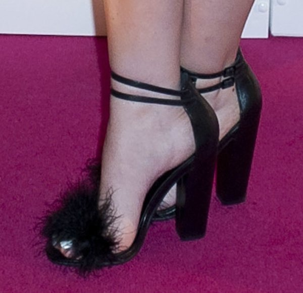 Perrie Edwards wearing black sandals that feature a striking feather design on the front straps
