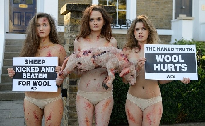 Models from animal rights group PETA are body painted to look bruised and bloodied with one holding a dead lamb at the start of UK Wool Week