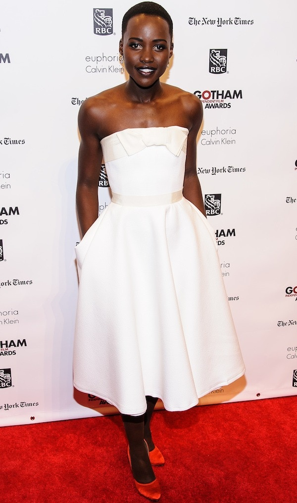 Lupita Nyong'o removed her coat to reveal her strapless white frock from Lanvin