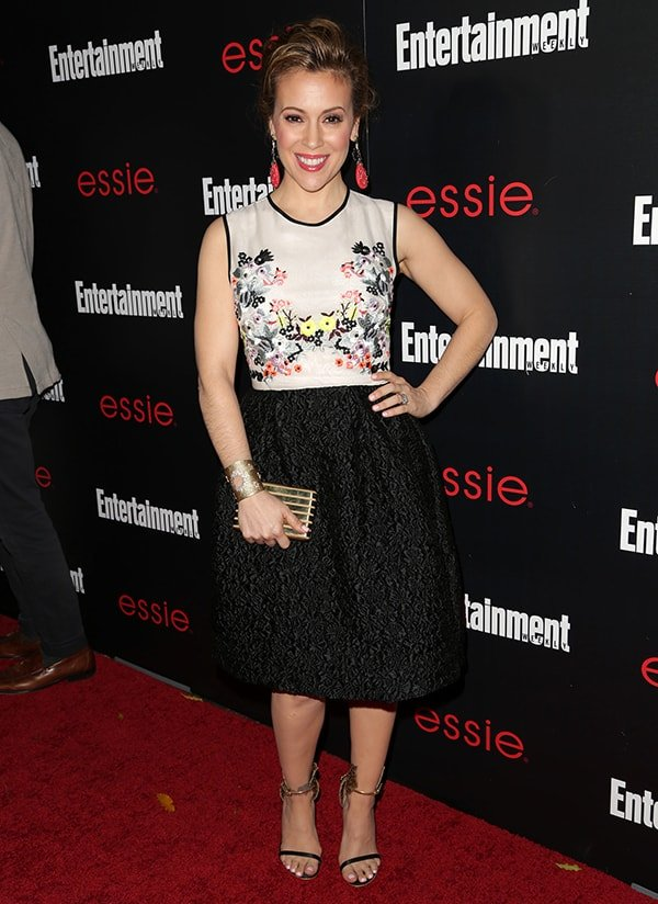 Alyssa Milano opted to look sweet and a lot younger than her age in an Erdem Resort 2014 dress that features a white bodice with floral embroidery and a textured black skirt with soft pleating