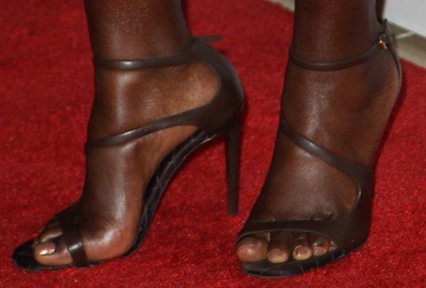 Lupita Nyong'o wearing asymmetric strappy Stella McCartney vegan leather sandals