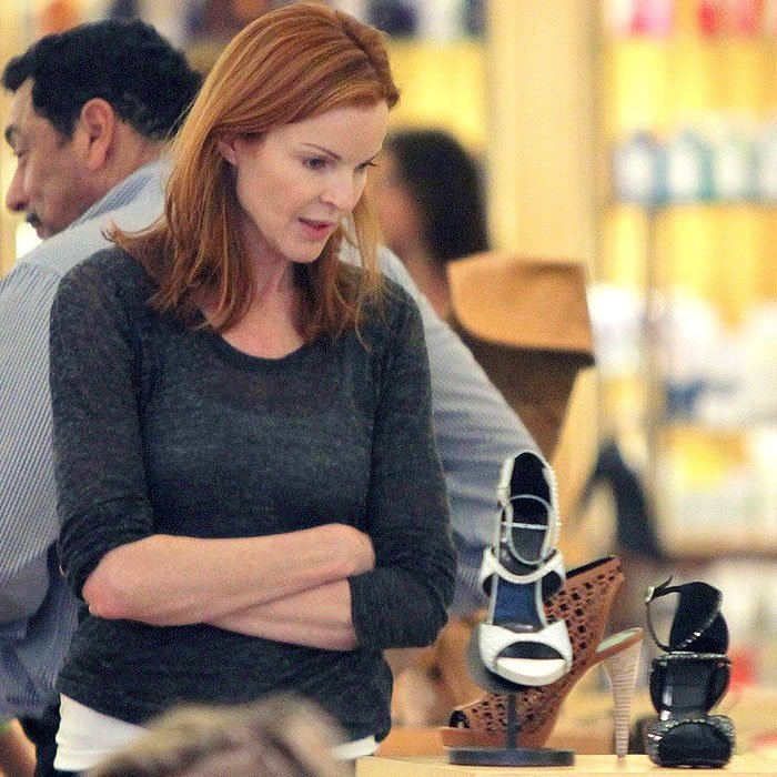 Marcia Cross scrutinizing a shoe on display at Barneys New York in Beverly Hills, California, on March 6, 2010