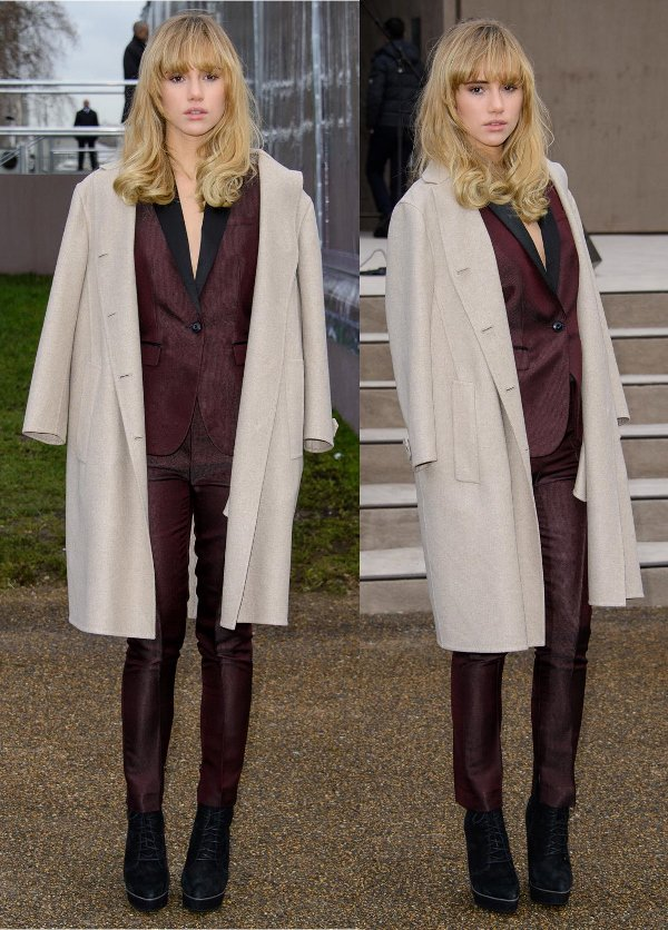 Suki Waterhouse took style inspiration from the boys by wearing a tailored satin burgundy suit with a cream wool coat