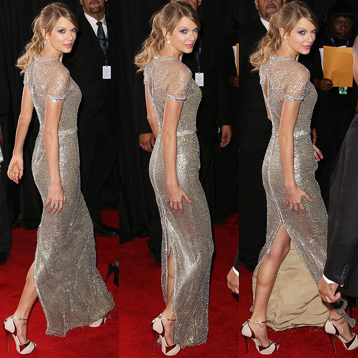 Taylor Swift's Gucci Première column gown is already too fab by itself, thanks to its crystal neckline, a crystal waist, and crystal sleeve cuffs binding the crystal mesh overlay, but that didn't stop her from wearing huge diamond earrings and metallic eye makeup