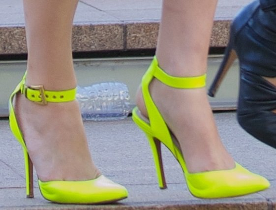 Alexandra Daddario wearing bright neon yellow ankle-wrap heels