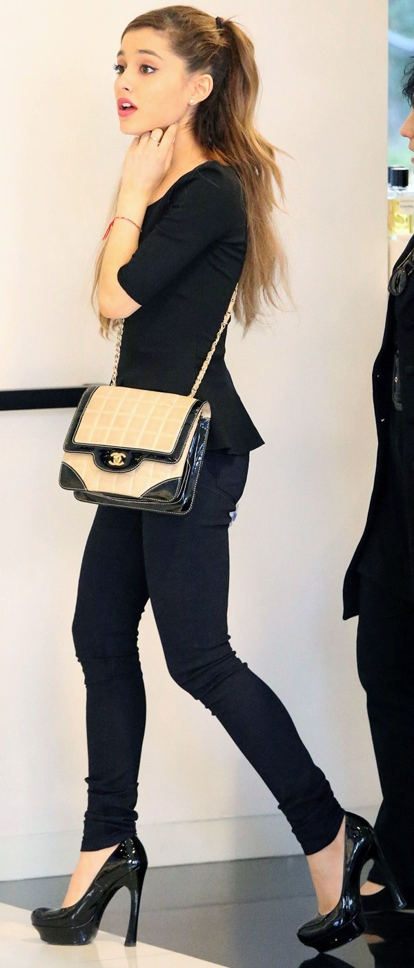 Ariana Grande accessorized with a small Chanel handbag and black platform pumps with funky flared heels