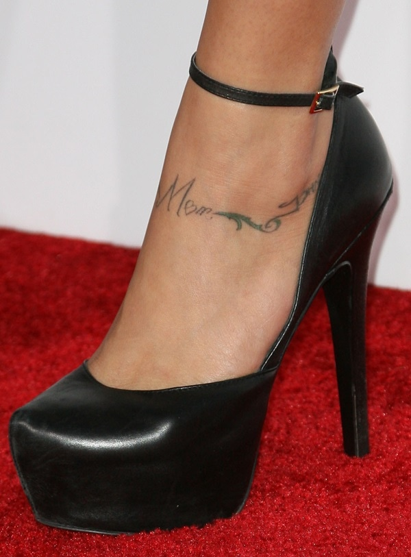 Cassie Scerbo showing off her foot tattoo in black ankle-strap platform pumps