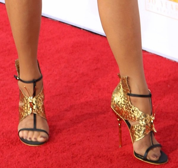 Christie Brinkley showing off her feet in gold-detailed t-strap sandals