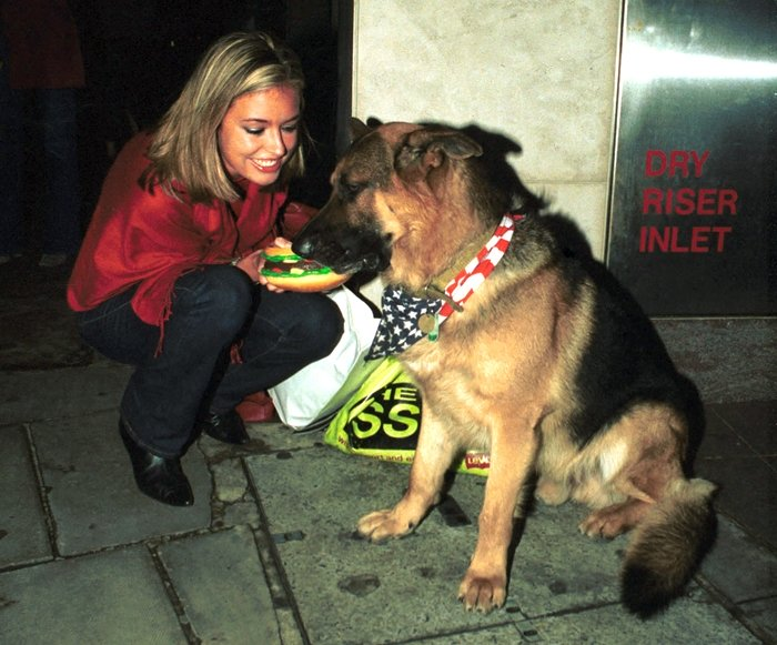 Cat Deeley meets the famous German shepherd Oscar the Met Bar dog on May 26, 1998, in London, England