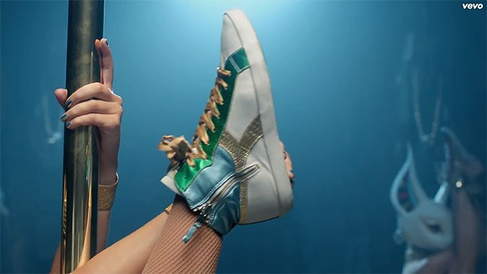 Katy does high kicks and splits in a pair of green-gold-and-blue high-top sneakers by Diadora