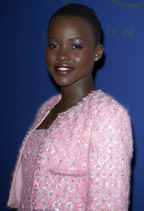 Lupita wearing a pink tweed frock with a matching cropped jacket
