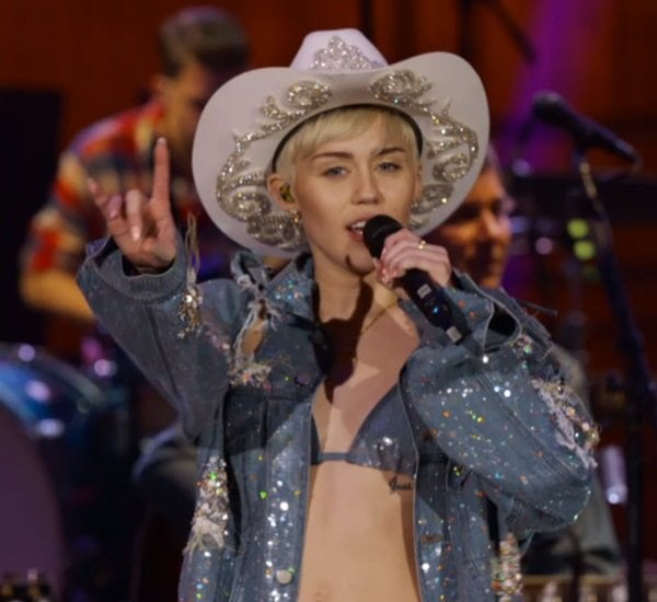 Miley Cyrus wearing a distressed denim jacket with a bikini top