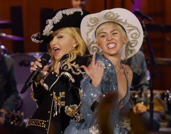 Miley Cyrus performing on stage with Madonna