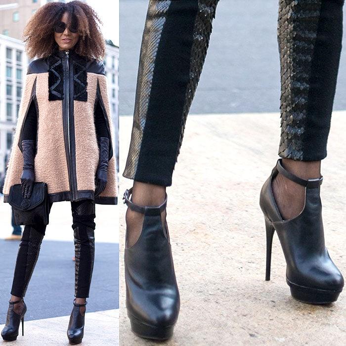 Model wears a cape coat, clutch, and snakeskin leggings