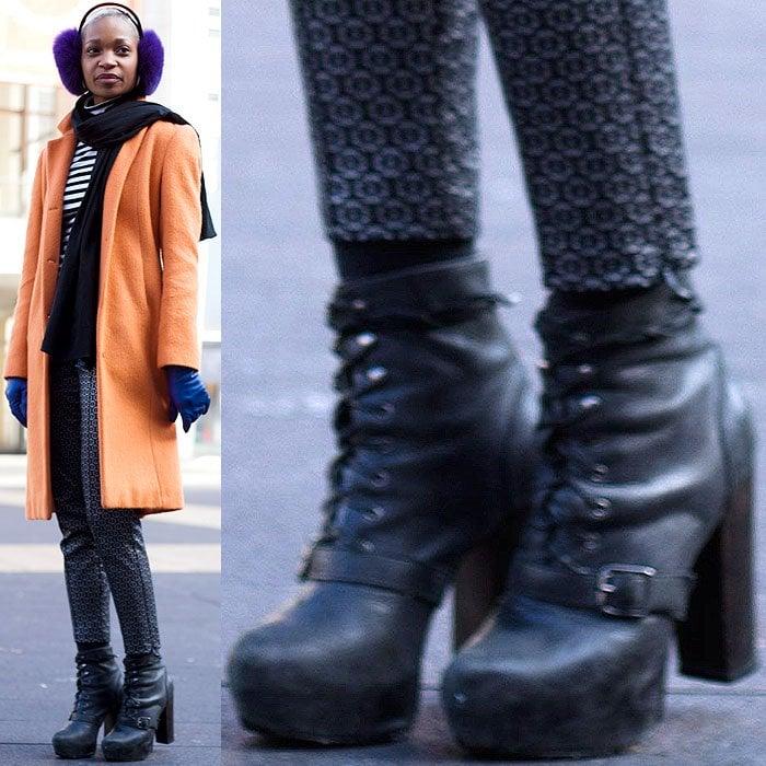 Model wears an orange coat, blue gloves, and purple earmuffs