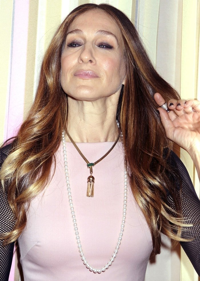 Sarah Jessica Parker wears a pink pleated dress detailed with mesh sleeves and black lace trimming at the hem