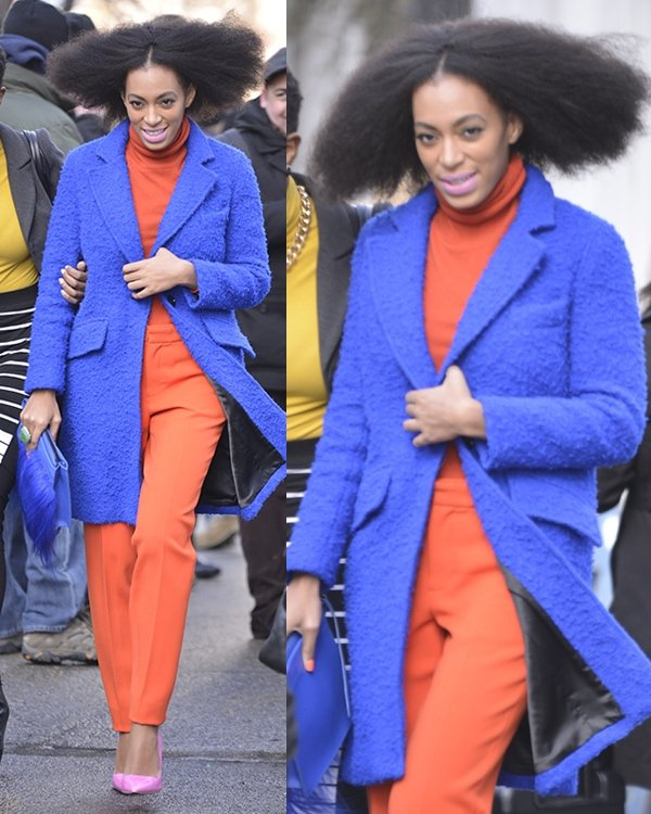 Solange Knowles wearing an orange turtleneck top with matching trousers styled with an electric blue Milly coat and a matching faux fur clutch