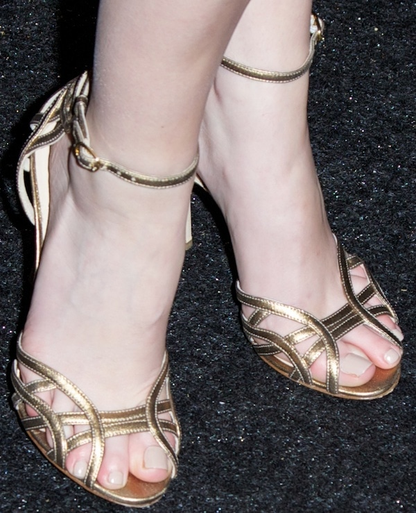 Anna Kendrick showing off her feet in gold ankle-strap sandals