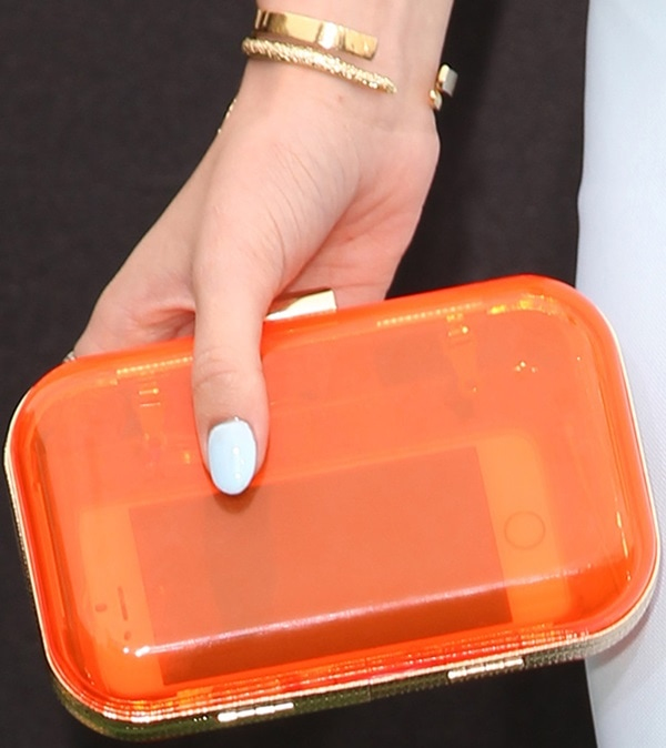 Bella Thorne toting an orange clutch