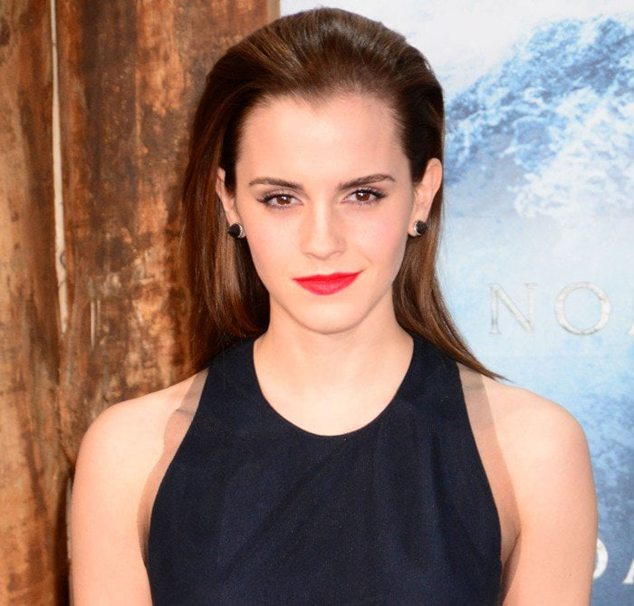 Emma Watson keeps things simple with a slicked-back hairstyle and earrings