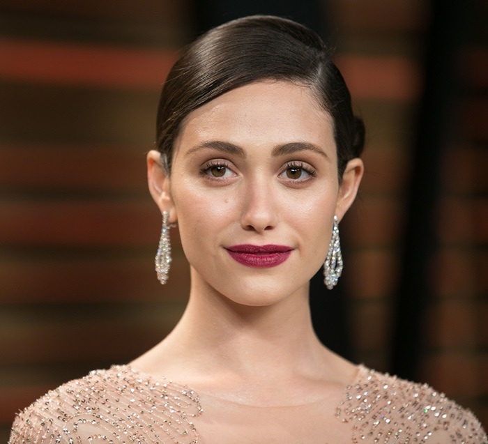 Emmy Rossum'shair was styled in a chic updo to show off her stunning statement earrings and dramatic red lips