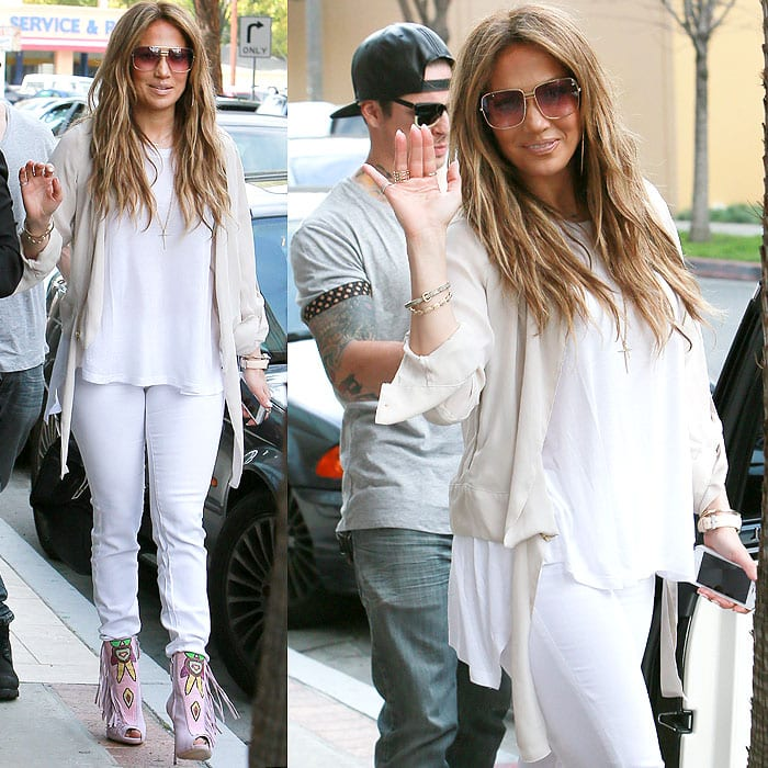 Jennifer Lopez waves to the paparazzi in an all-white ensemble with pink beaded booties