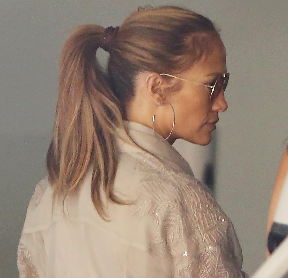 Jennifer Lopez wears Gucci Gg 2235 sunglasses and Jennifer Fisher flat thread hoops earrings