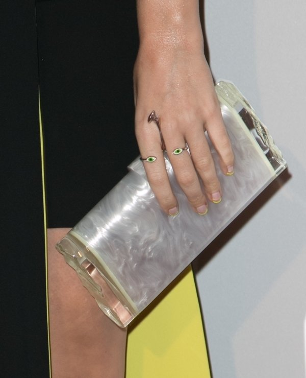 Katy Perry showing off her jewelry and clutch handbag