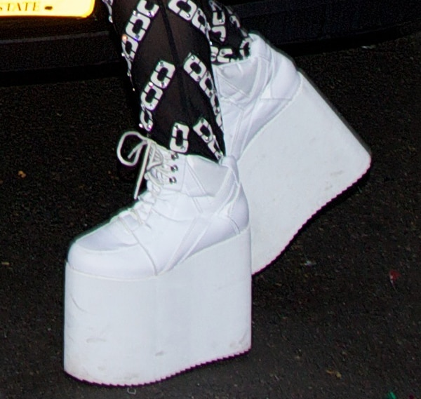 Lady Gaga wearing white lace-up sneakers with towering platforms
