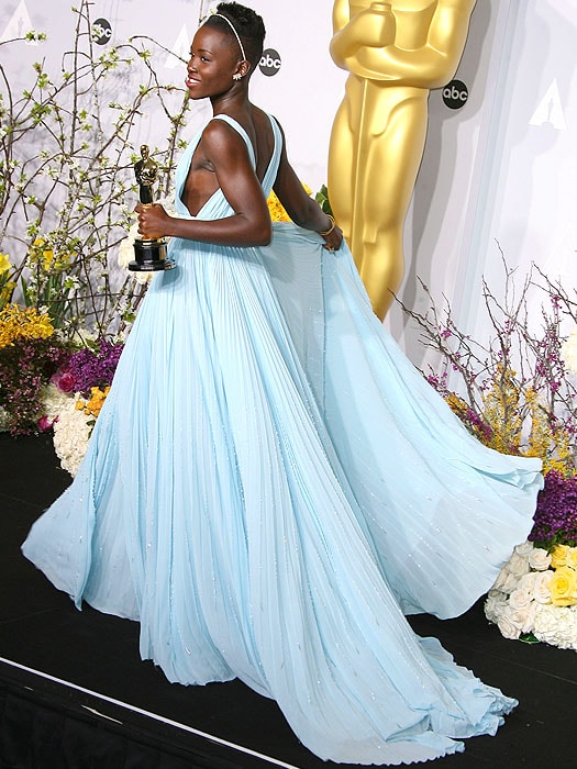 When she stepped into the flower-filled press room with her Oscar in hand, we half-expected birds to come out singing because she really did remind us of Cinderella among all those bouquets.