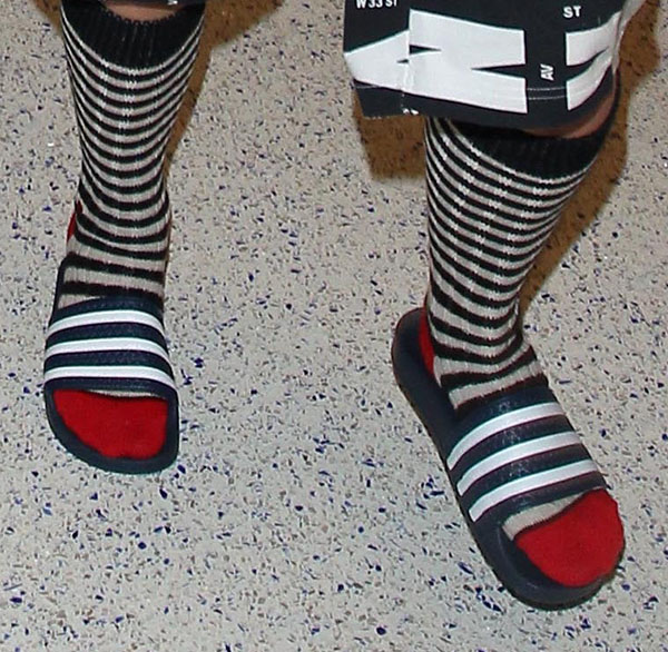 "Rita Ora wearing adidas ""Adilette"" pool slide sandals with striped red-toed socks"